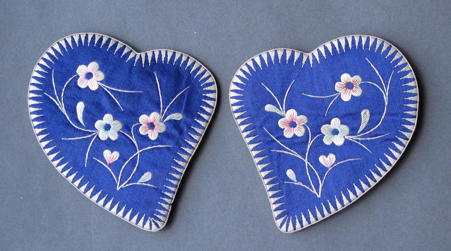 A pair of Chinese silk ear muffs with flower embroidery c1920