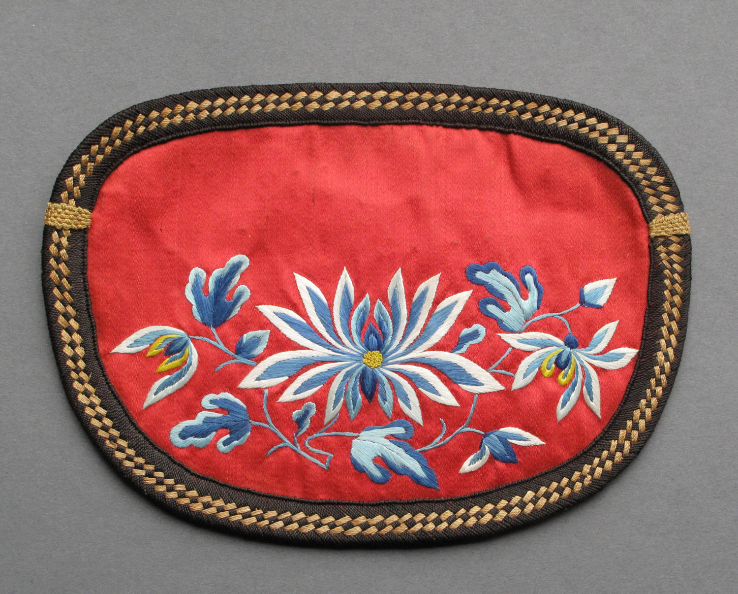 A late C19th red Chinese silk purse with blue flower decorations