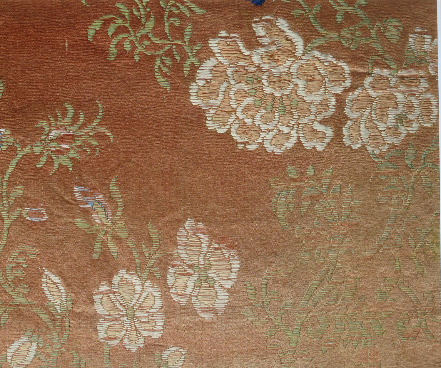 A mounted early C18th Chinese woven silk panel with peony flowers