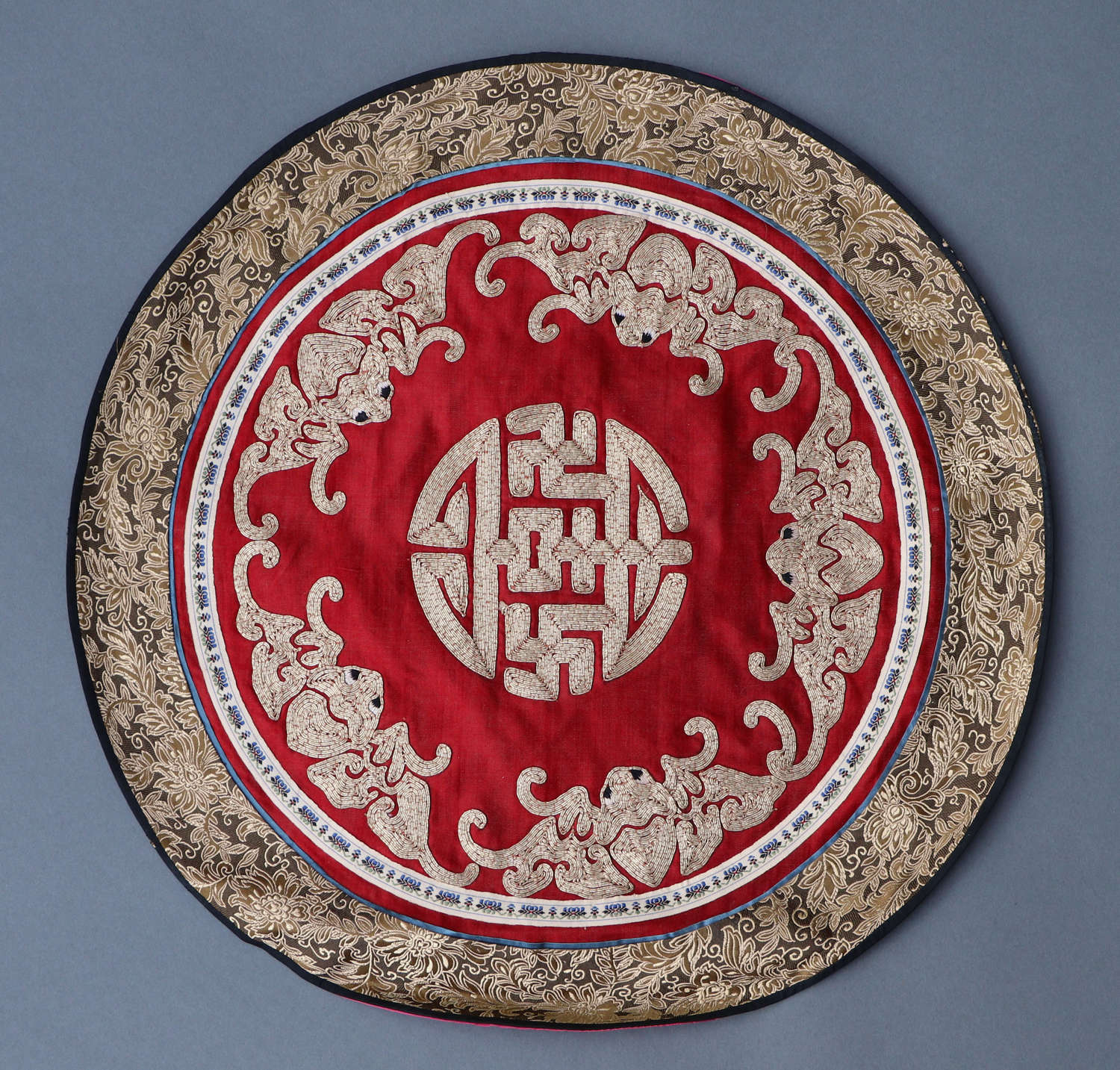 An early 20th century Chinese embroidered red silk roundel